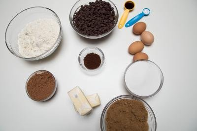 Ingredients on table including; 4 eggs, 2 sticks of butter, a bowl with chocolate chips, a bowl with sugar, a bowl of cocoa, a bowl with sugar, a bowl with instant coffee, a bowl with flour, and a measuring spoon with vanilla extract, and baking powdered