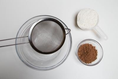 A bowl with a strainer on top and cocoa and flour besides the bowl