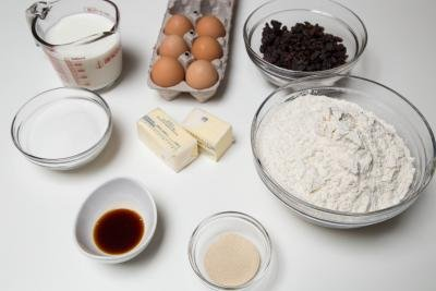 Ingredients on table including; 2 sticks of butter, 6 eggs, a measuring cup of milk, a bowl of flour, bowl of yeast, bowl of sugar, bowl of raisins, and a bowl of vanilla extract