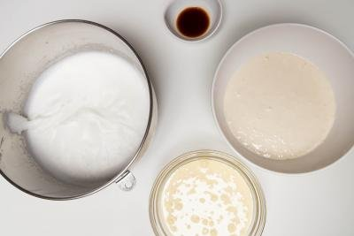 Whisked sugar and egg whites in a mixing bowl, 2 bowls with milk, yeast and flour mixture, and vanilla extract in a small bowl