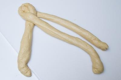 Dough in 3 long snake rolls being braided