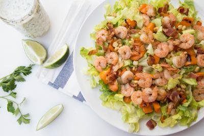 Shrimp Lettuce Salad on a large plate, with a jar of ranch dressing next to it and limes