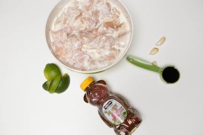 Ingredients on table including; honey, pieces of chicken in ranch in a bowl, lime wedges, 3 garlic cloves and a measuring spoon with soy sauce