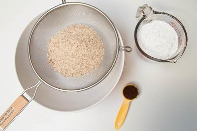 Powdered sugar and almond flour being sifted, with a measuring spoon with instant coffee next to the bowl into which everything is being sifted into