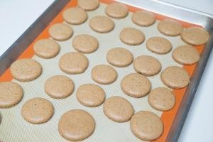 Coffee Macarons on a lined baking sheet