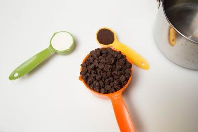 3 measuring spoons one with chocolate chips, another with instant coffee and the third with heavy whipping cream