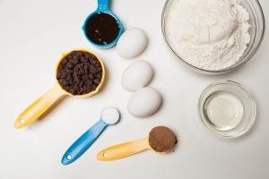 Ingredients on table including; 3 eggs, a bowl with flour, a bowl with Irish liqueur, a measuring spoon with chocolate chips, another with cocoa, the third with baking soda , and fourth with honey