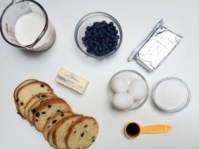 Ingredients on table including; slices of bread, 3 eggs in a bowl, a stick of butter, a package of cream cheese, a bowl of blueberries, sugar in a bowl, milk in a measuring cup and vanilla extract in a measuring spoon