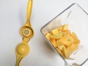 Mango in a blender and lemon half in a lemon squeezer