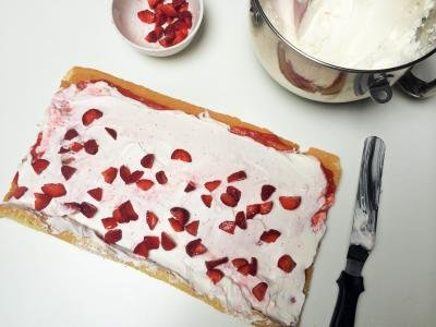 Sliced strawberries spread on top of the cream on the cake