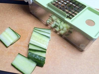 Cucumbers being diced using a plastic veggie dicer