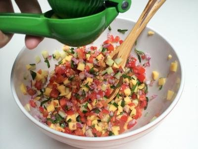 A lime being squeezed into a bowl with the salsa mixture