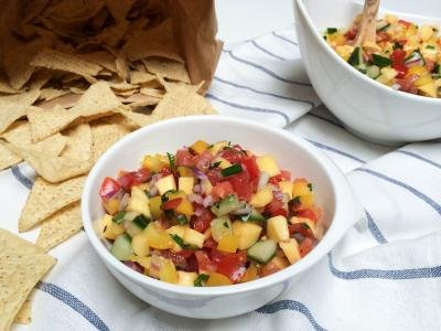 Mango Salsa in a bowl with chips next to the bowl