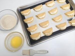 Sweet Cheese Cookies on a baking pan that is lined with a silicon mat, with 2 bowls next to it one with sugar and the other with melted butter and a pastry brush next to the bowls
