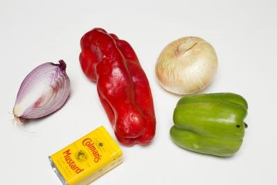 Ingredients on the table including; a red and green bell pepper, 1/4 of a purple onion, a full yellow onion and Colman's mustard
