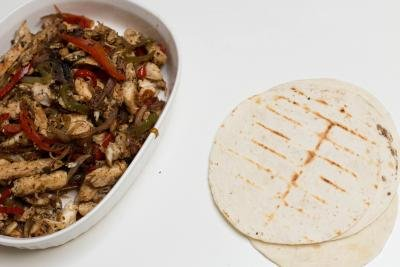 Chicken Fajitas in a pan with tacos next to it