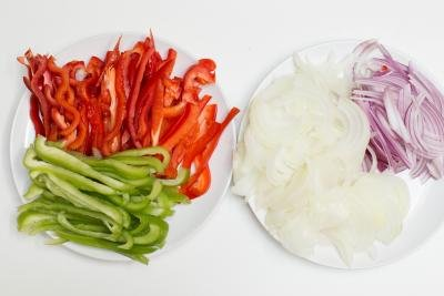 Green and red bell peppers cut into long thin slices on a plate, and red and white onions cut into half rings on a plate