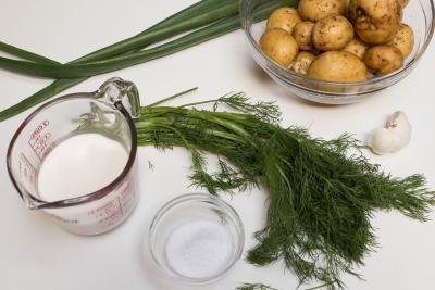 Ingredients on table including; potatoes in a bowl, dill, green onions, salt in a bowl, garlic, and cup of whipping cream