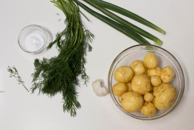 Ingredients on table including; potatoes in a bowl, dill, green onions, salt in a bowl, and garlic