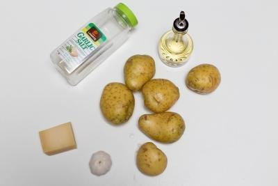 Ingredients on table including; potatoes, garlic, parmesan, oil and garlic salt