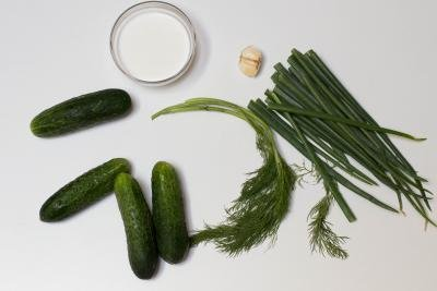 Ingredients on table including 4 cucumbers, dill, green onion, 3 cloves of garlic, and a bowl with sour cream