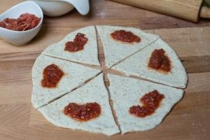 Rolled out pizza dough cut into 6 even triangle slices and marinara sauce placed on each of them
