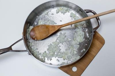 Diced onions being sautéed in a deep skillet