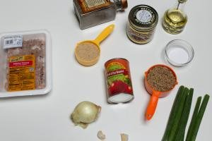 Ingredients on the table including; an onion, green onions, 2 garlic cloves, a can of tomatoes, a measuring cup with lentils, a small bowl salt, a measuring cup with bread crumbs, a jar of better than boullion, oil, pepper, and ground turkey