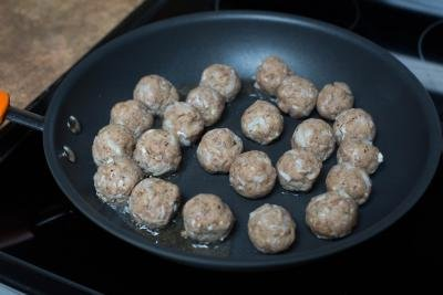 Meatballs being fried on a skillet