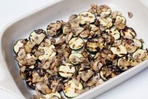 Sautéed mushrooms placed on top of the zucchini rings in a baking pan