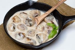 Meatballs in a Cream Sauce in a small iron cast pan with a wooden spoon in the sauce