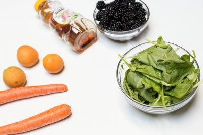 Vegetables and fruits on the table including; spinach in a bowl, 2 carrots, 3 apricots, a bowl of blackberries and honey