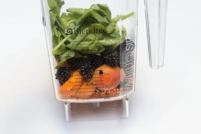 Fruits, veggies and honey being blended in a blender