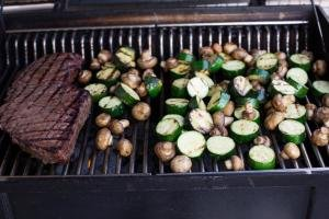 Seasoned zucchini and Mushrooms on a grill with a steak next to them