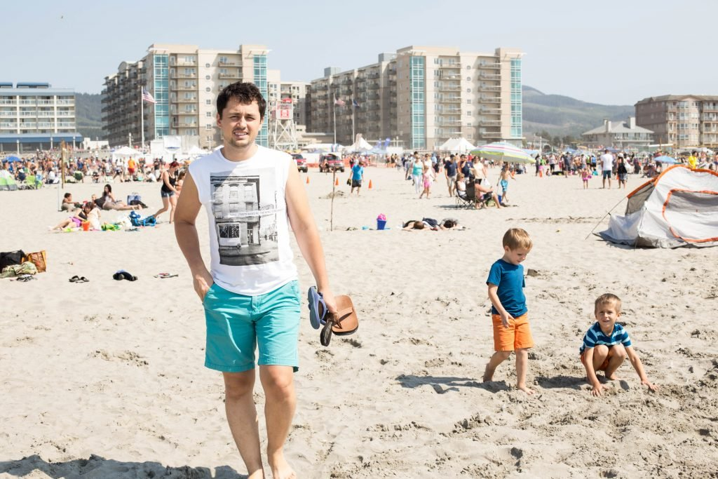 A man on the beach with many people and hotels in the background