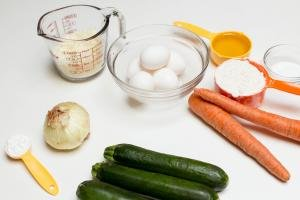 Ingredients on table including; a measuring cup with mozzarella cheese, a bowl with 5 eggs. an onion, 3 zucchinis, 2 carrots, 3 measuring spoons one with baking powder, another with flour and the third with oil and a bowl of salt