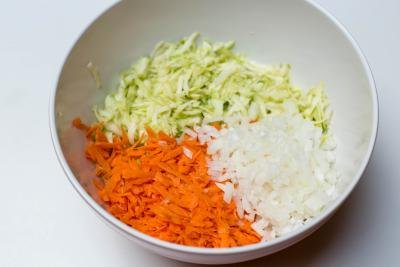 In a large bowl there are grated zucchini and carrots and diced onions