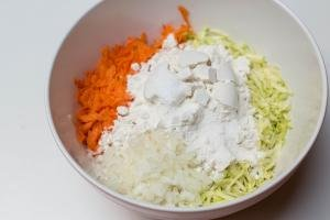 Flour and baking powder added to the veggies in the mixing bowl