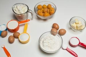 Ingredients on the table including; flour in a bowl, 6 eggs, a bowl with butter, a bowl with apricots, a measuring cup with farmers cheese, and 6 measuring spoons with sugar, baking powder, whipping cream, potato starch