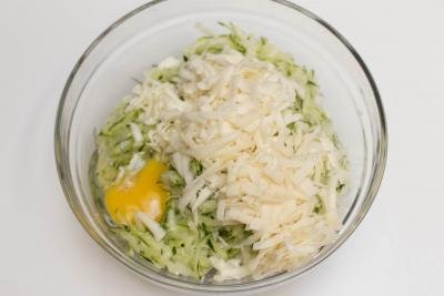 Grated zucchini, parmesan, mozzarella, and an egg in a bowl