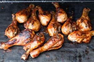 Chicken drumsticks on the grill with BBQ put over the top of them