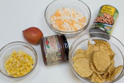 Ingredients on table including; corn in a bowl, chips in a bowl, spicy clack bean dip in a jar, a tomato, a jar of pinto beans, and a bowl of cheese