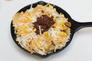 Beans placed on top of the chips, corn and cheese