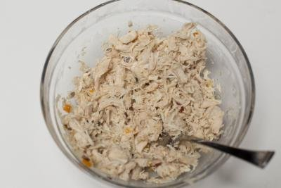 Cooked chicken pulled apart in a bowl