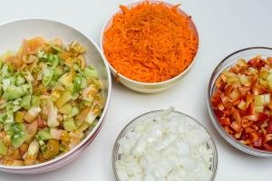 4 bowls one with diced tomatoes, one with diced onions, one with diced peppers and the fourth with shredded carrots