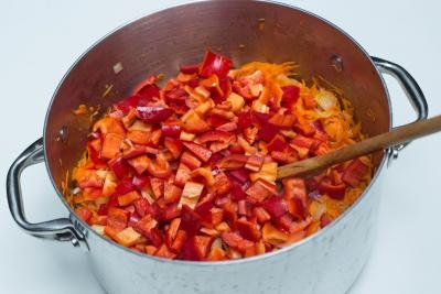Diced peppers added to the large pot with shredded carrots and onions