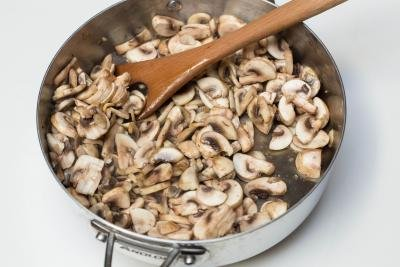 Diced mushrooms being sautéed in a deep skillet