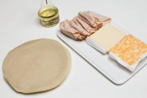 Ingredients on table including; tortillas, 2 different kinds of cheese in slices, and deli meat