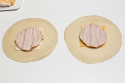 Cheese and deli meat placed in the middle of a tortilla