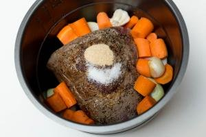 Beef in a crock pot with veggies and seasoning added to it